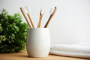 four bamboo toothbrushes sit in a white cup on a countertop
